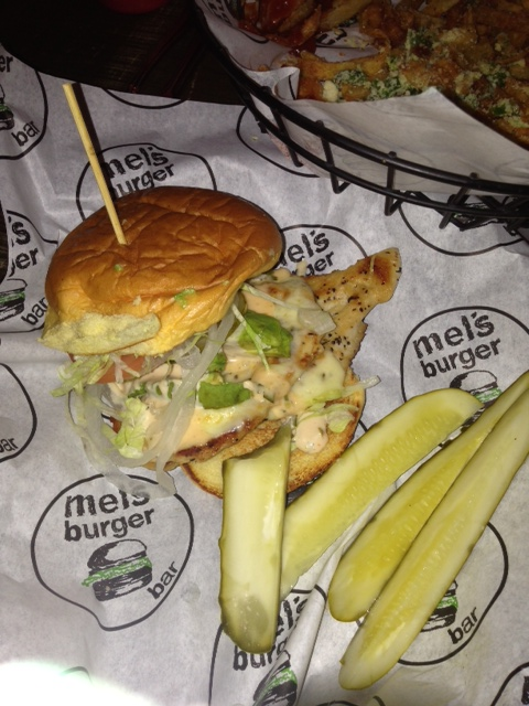 grilled chicken sandwich with avocado, onions, some kind of sauce and pickles