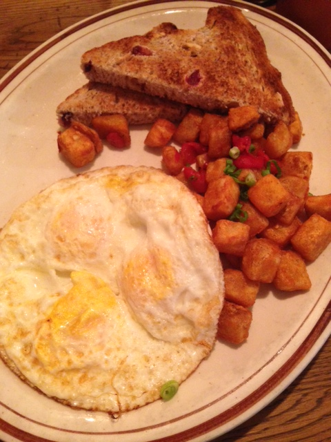 runny eggs, potatoes with peppers and cranberry whole wheat toast